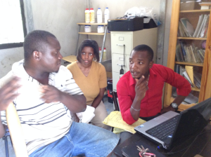 Volunteer Jen Pettie (center) reviews financial statements with business owner Marc-Nes Desir (left) and translator Louis Brunel (right)