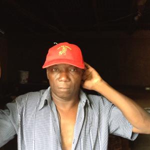 "Haitian entrepreneur Andre Louissant wears a cap promoting his business, ""Top Bakery."""